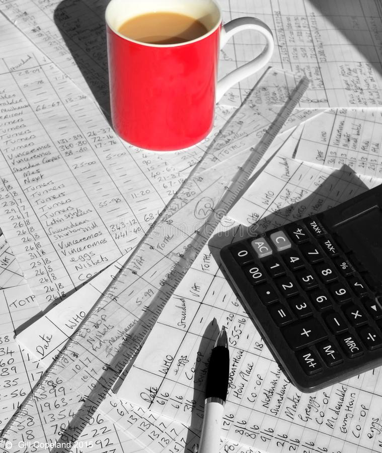 Tazza da caffè rossa sopra le carte piene di per la matematica scritto mano e del calcolatore immagini stock