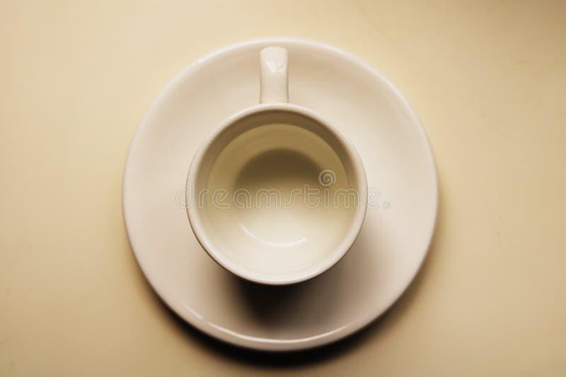 Tazza da the e piattino bianchi vuoti su una superficie bianca della tavola - vista superiore della regolazione della prima colaz fotografie stock libere da diritti