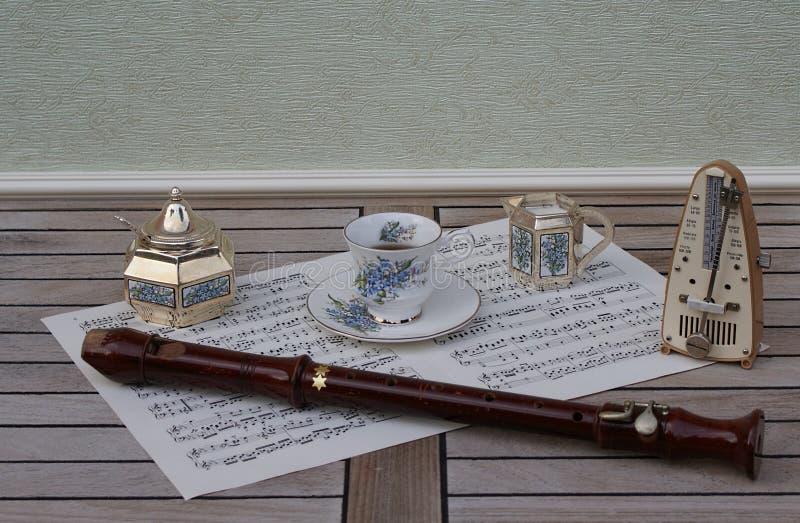 Tazza da the e piattino inglese, brocca crema, ciotola di zucchero, cucchiaio di zucchero e metronomo per musica e una flauto del fotografie stock libere da diritti