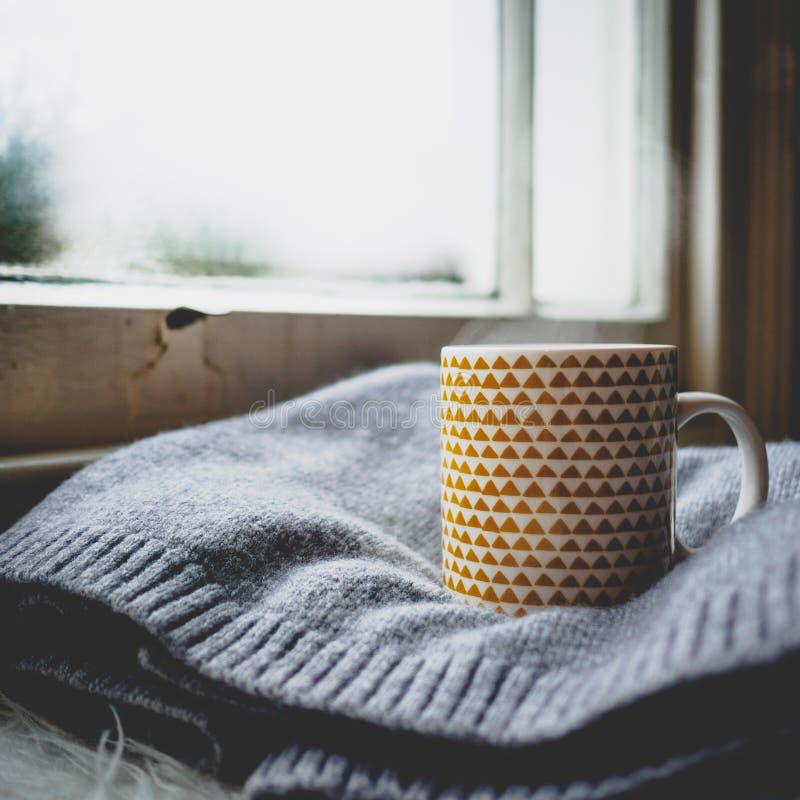Tazza decorata con gli elementi geometrici gialli su un maglione della lana davanti ad una finestra di telaio fotografia stock