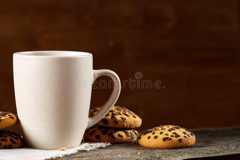 Tazza dei biscotti di pepita di cioccolato e del tè sul tovagliolo homespun bianco nel fuoco stile country e selettivo fotografia stock libera da diritti