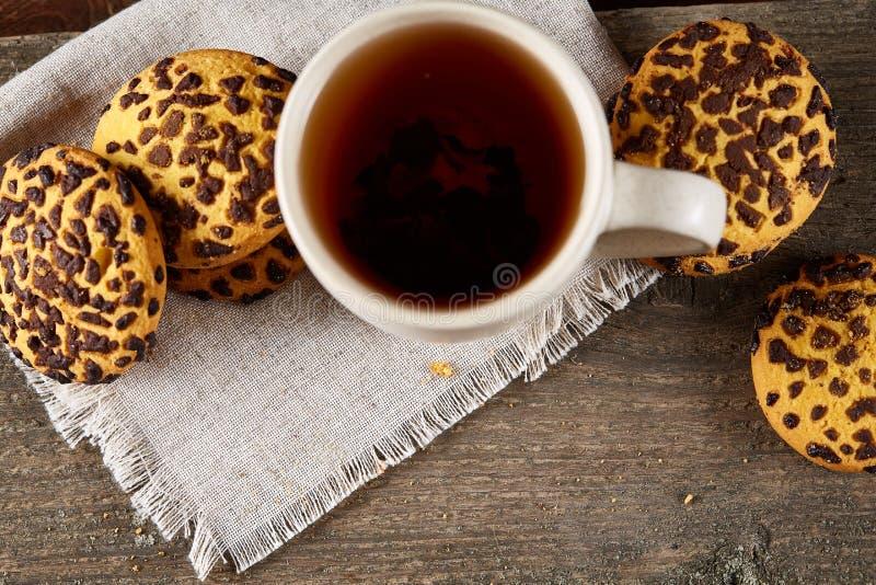 Tazza dei biscotti di pepita di cioccolato e del tè sul tovagliolo homespun bianco nel fuoco stile country e selettivo immagini stock libere da diritti
