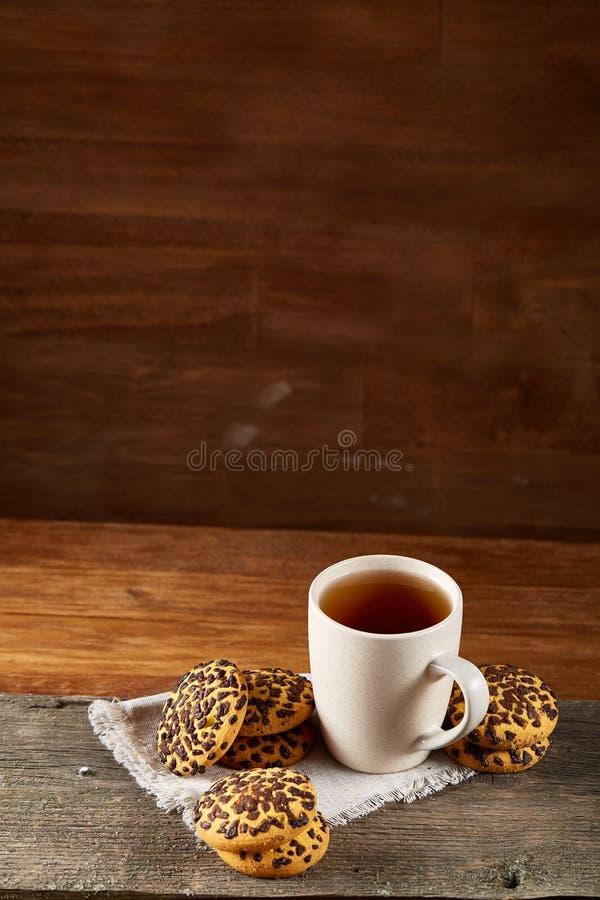 Tazza dei biscotti di pepita di cioccolato e del tè sul tovagliolo homespun bianco nel fuoco stile country e selettivo fotografia stock