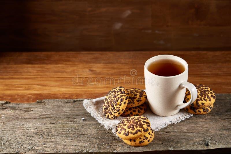 Tazza dei biscotti di pepita di cioccolato e del tè sul tovagliolo homespun bianco nel fuoco stile country e selettivo immagini stock