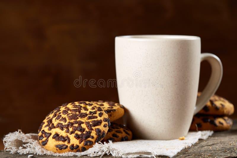 Tazza dei biscotti di pepita di cioccolato e del tè sul tovagliolo homespun bianco nel fuoco stile country e selettivo fotografie stock