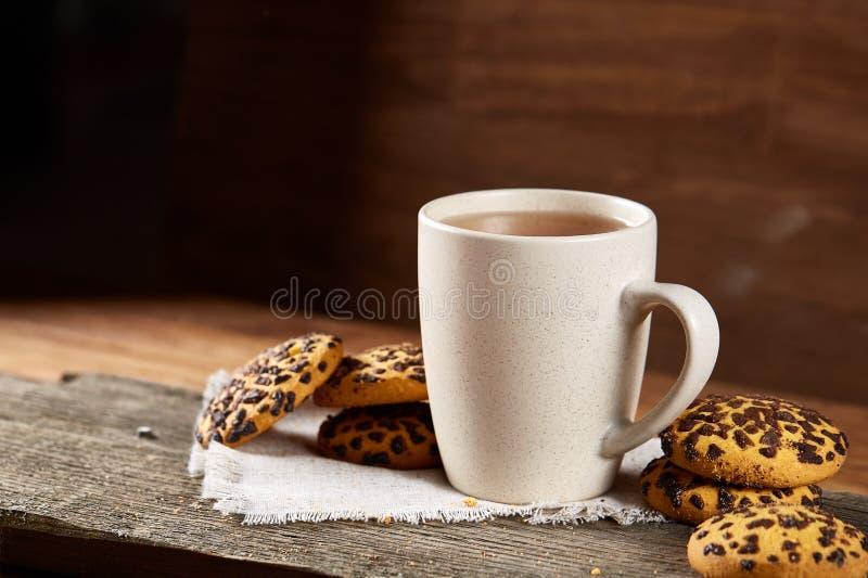 Tazza dei biscotti di pepita di cioccolato e del tè sul tovagliolo homespun bianco nel fuoco stile country e selettivo immagine stock