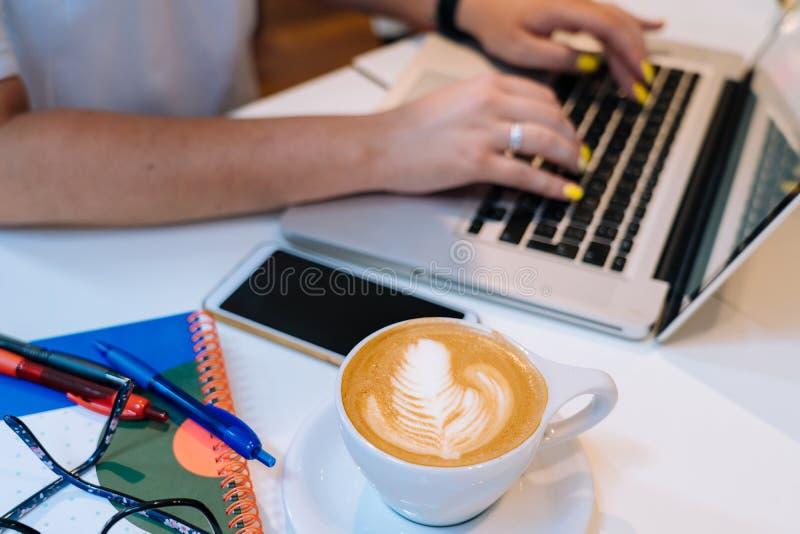 Tazza del caffè del cappuccino e della donna delle mani che si siedono nell'ufficio che coworking e che scrive sul suo computer d fotografia stock