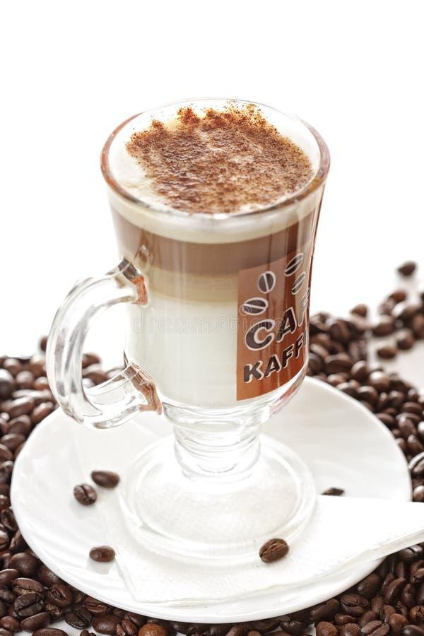 Tazza del caffè del latte sui fagioli fotografia stock