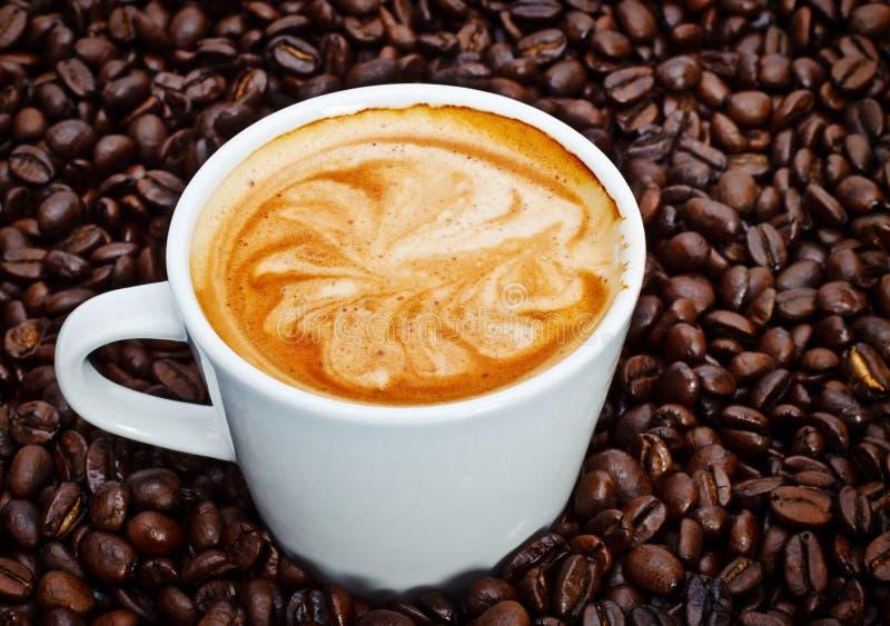 Tazza del caffè espresso in chicchi di caffè fotografia stock libera da diritti