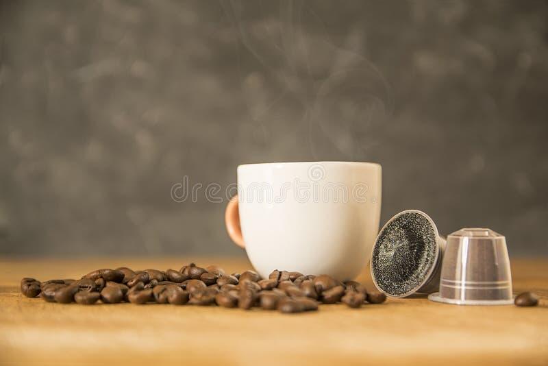 Tazza del caff? macinato caldo e del caff? in capsule dai chicchi di caff? su una tavola di legno di una cucina rustica Fumo, aro immagine stock
