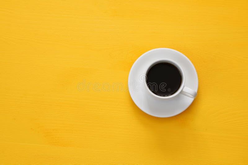 tazza del coffe su fondo giallo di legno fotografie stock
