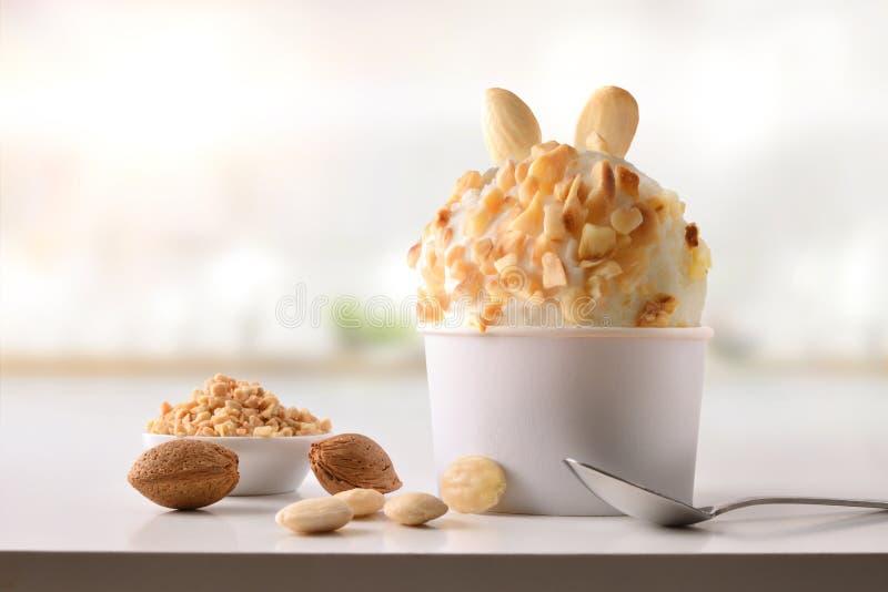 Tazza del gelato della mandorla sulla tavola bianca casalinga in cucina immagine stock libera da diritti