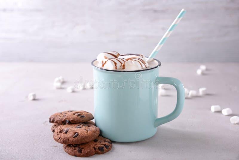 Tazza del metallo della bevanda deliziosa del cacao con le caramelle gommosa e molle ed i biscotti sulla tavola fotografie stock libere da diritti