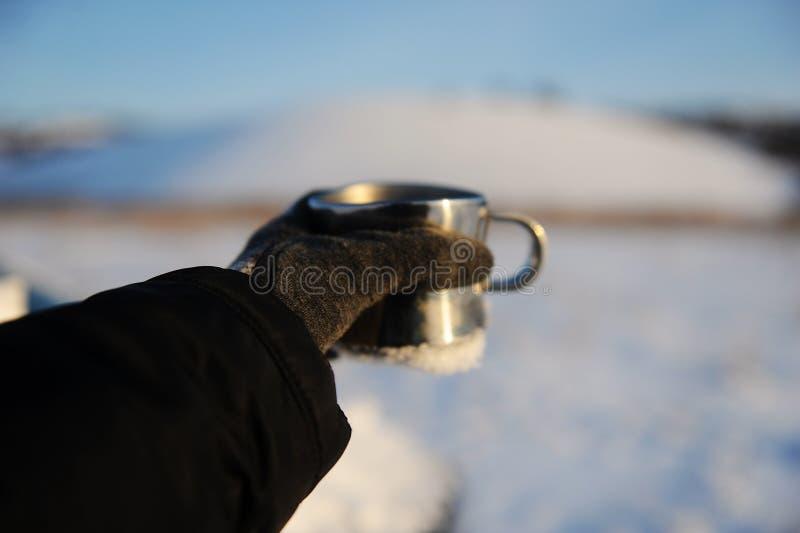 Tazza del metallo in una mano tesa sui precedenti di un paesaggio russo della neve di inverno Chiaro cielo blu fotografia stock libera da diritti