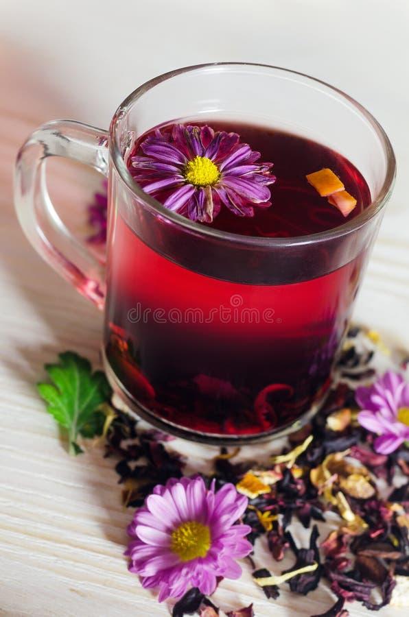 Tazza del tè dell'ibisco con i frutti asciutti su fondo di legno bianco immagine stock