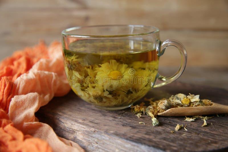 Tazza del tè di camomilla con la camomilla in cucchiaio su fondo di legno rustico fotografie stock libere da diritti