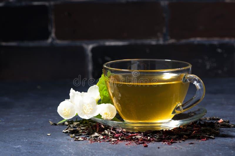 Tazza del tè fragrante del gelsomino su un fondo scuro immagini stock libere da diritti