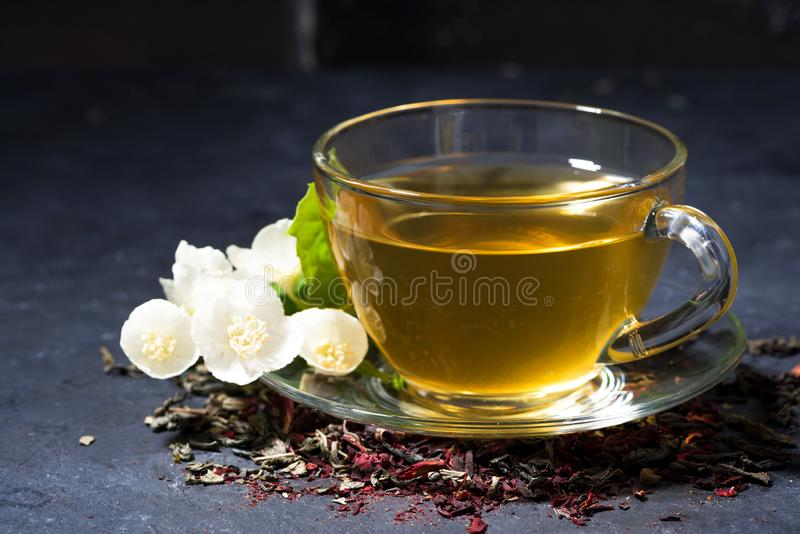 Tazza del tè fragrante del gelsomino su una tavola scura fotografia stock