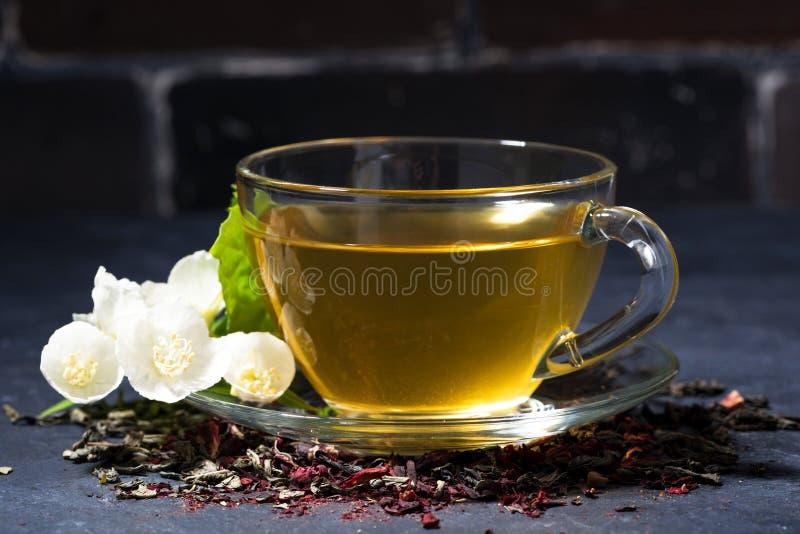 Tazza del tè fragrante su un fondo scuro, primo piano del gelsomino immagini stock