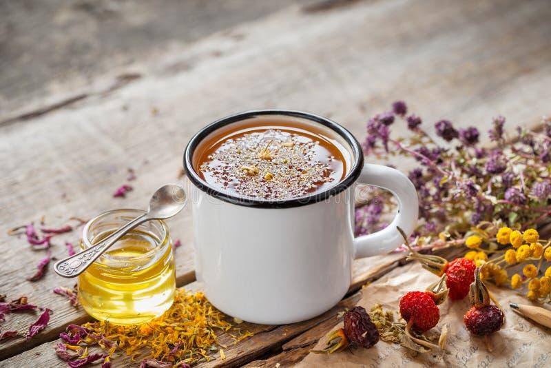 Tazza del tè sano della margherita, del miele e delle erbe curative sulla tavola immagini stock libere da diritti