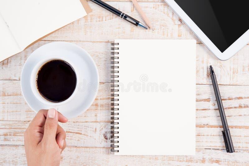 Tazza del taccuino caldo di scrittura della mano dell'uomo e del caffè su backgr di legno immagine stock