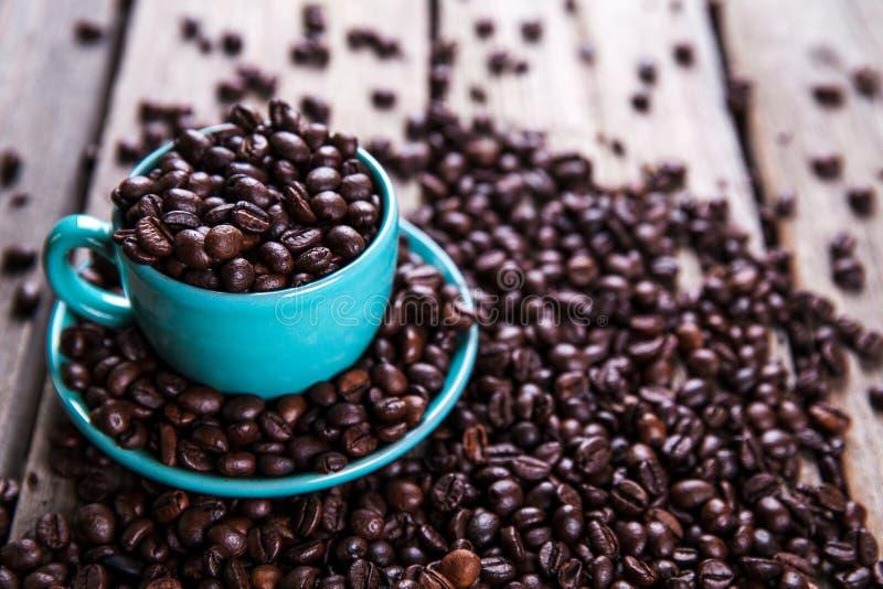 Tazza del turchese con i chicchi di caffè su un fondo di legno Bevanda, stoviglie fotografia stock libera da diritti