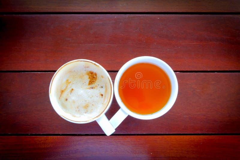 Tazza deliziosa fino alla tazza di caffè completamente vuota sulla tavola di legno fotografia stock