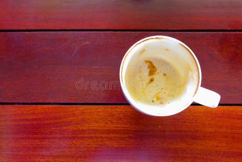Tazza deliziosa fino alla tazza di caffè completamente vuota sulla tavola di legno immagini stock libere da diritti