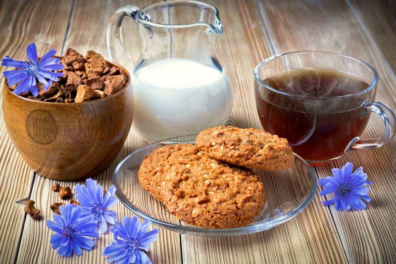 Tazza della bevanda della cicoria e fiori blu sui bordi di legno anziani fotografia stock libera da diritti