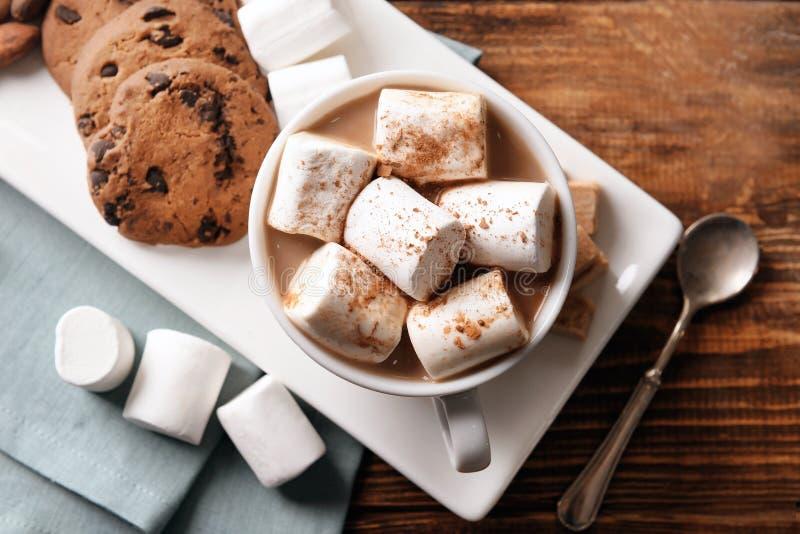 Tazza della bevanda deliziosa del cacao con le caramelle gommosa e molle ed i biscotti sul piatto, vista superiore fotografia stock