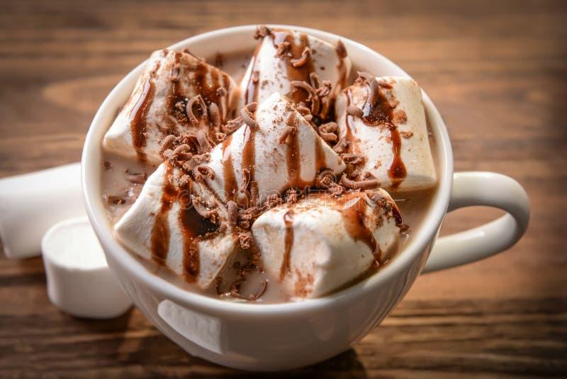 Tazza della bevanda deliziosa del cacao con le caramelle gommosa e molle sulla tavola di legno, primo piano immagini stock