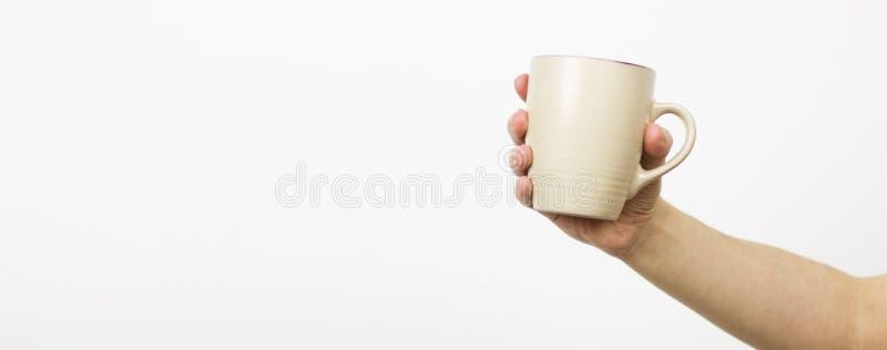 Tazza della tazza in mano femminile su isolamento bianco del fondo - fuoco selettivo, spazio della copia fotografia stock libera da diritti