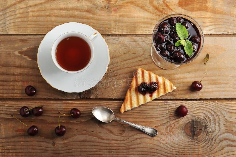 Tazza della marmellata di amarene e del tè, pane tostato del pane con inceppamento immagini stock libere da diritti