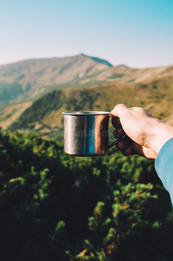 Tazza della tenuta dell'uomo di caffè caldo in montagne Fondo della montagna fotografie stock libere da diritti