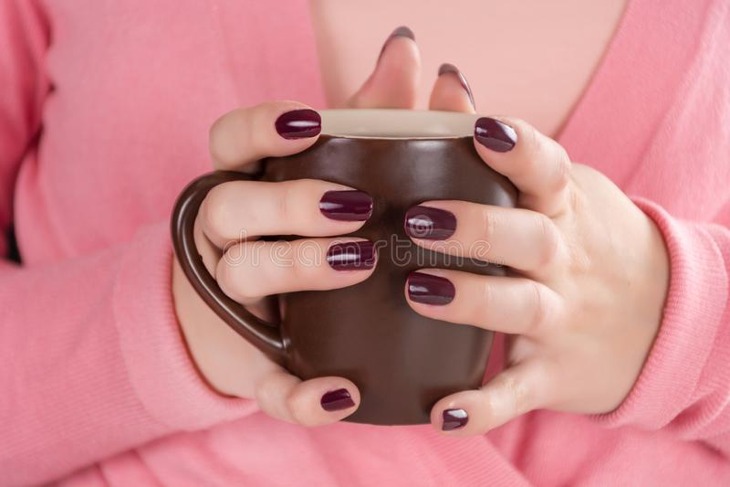 Tazza della tenuta della ragazza di tè a disposizione con la lucidatura di unghie del manicure di colore del vino rosso immagini stock libere da diritti