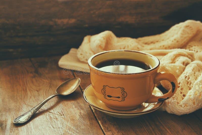 Tazza delle foglie di autunno del vecchio libro h di spirito del tè e di un maglione caldo sulla tavola di legno immagini stock