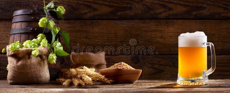 Tazza di birra con il luppolo di verde e le orecchie del grano fotografia stock libera da diritti