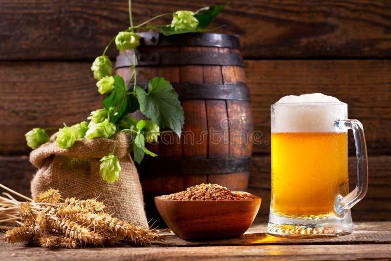 Tazza di birra con il luppolo verde, le orecchie del grano ed il barilotto di legno fotografie stock libere da diritti