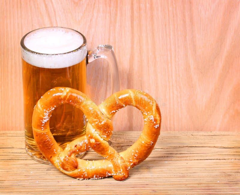 Tazza di birra con la ciambellina salata tedesca su fondo di legno fotografia stock libera da diritti