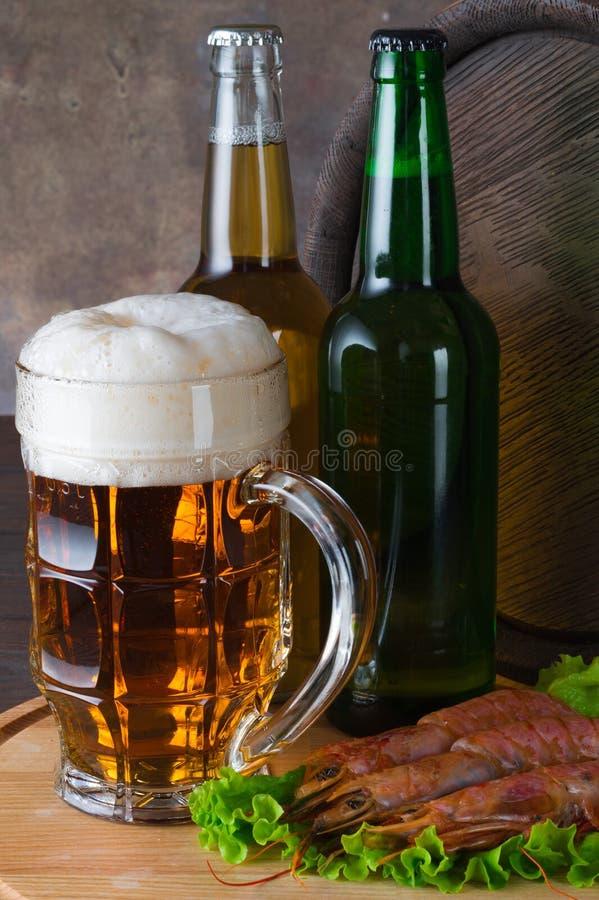 Tazza di birra con schiuma e delle bottiglie di birra, di gamberetto e di un barilotto su una tavola di legno e su una parete scu fotografia stock libera da diritti