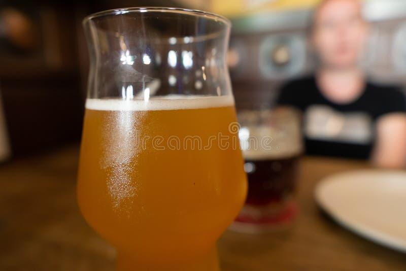 Tazza di birra fredda con vetro appannato Ragazza nella sfuocatura su fondo immagini stock