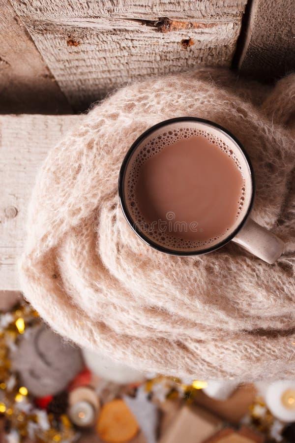 Tazza di cacao caldo, di marrone, della sciarpa tricottata su fondo woodan e dei dettagli di festa della sfuocatura, spazio della fotografia stock libera da diritti