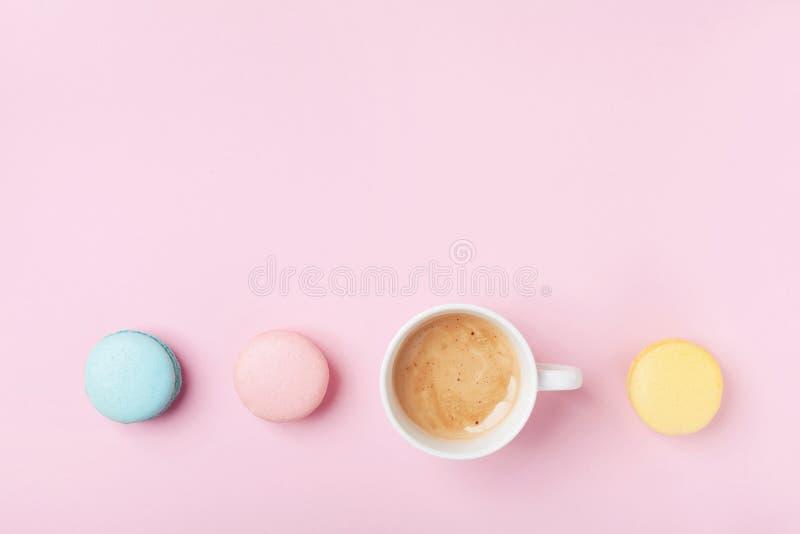 Tazza di caffè accogliente della prima colazione di mattina e macaron variopinto sulla vista superiore del fondo di rosa pastello immagini stock libere da diritti