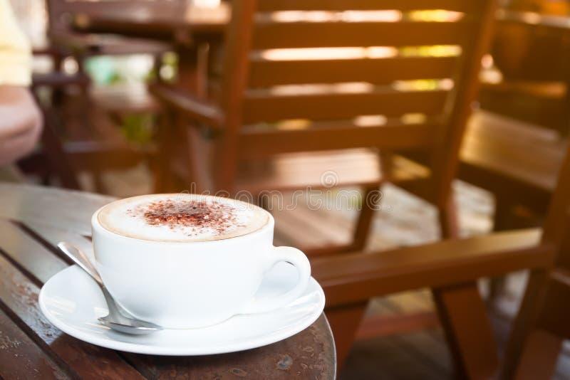 Tazza di caffè alta vicina sulla tavola di legno in caffè, spazio della copia con MOR fotografia stock