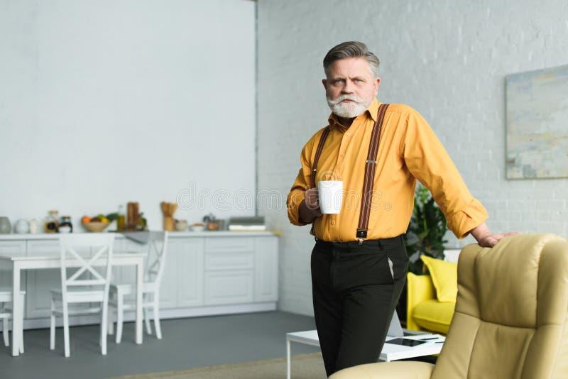 tazza di caffè barbuta alla moda della tenuta dell'uomo senior ed esaminare macchina fotografica fotografia stock libera da diritti