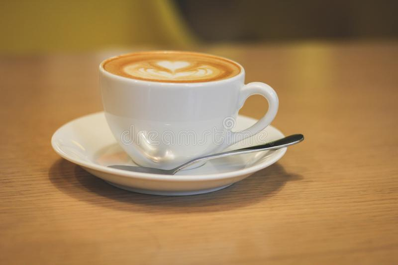 Tazza di caffè bianca della porcellana con un piattino e un cucchiaio fotografia stock libera da diritti