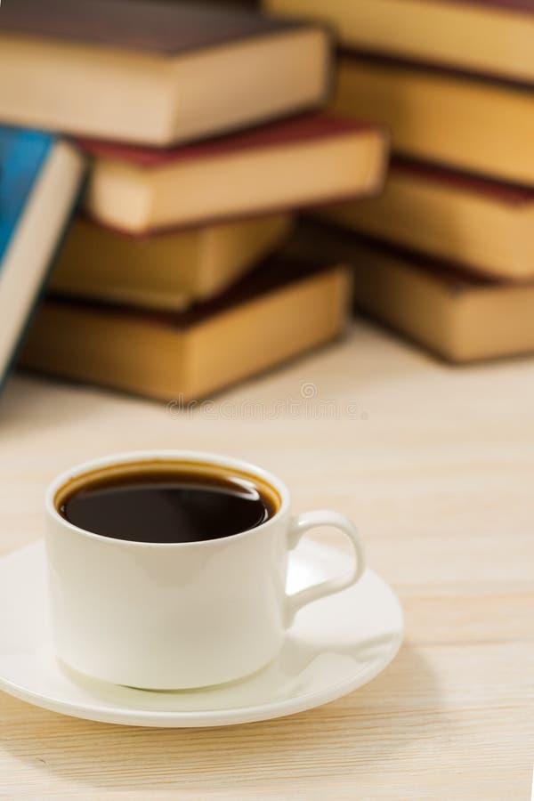 Tazza di caffè bianca su una tavola accanto ai libri fotografie stock libere da diritti