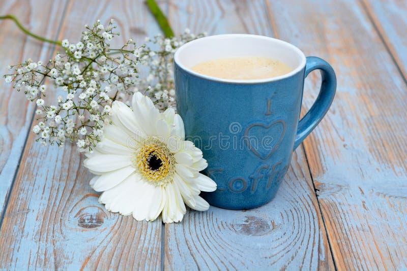 Tazza di caffè blu d'annata su un fondo di legno con la decorazione bianca della margherita della gerbera fotografia stock libera da diritti