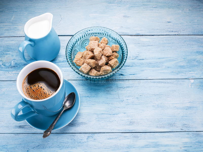 Tazza di caffè, brocca di latte e cubi dello zucchero di canna fotografia stock libera da diritti