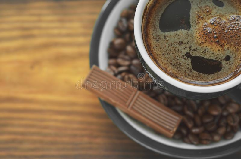 Tazza di caffè di Brown con una schiuma su un piattino con i chicchi di caffè con un pezzo di cioccolato fotografia stock
